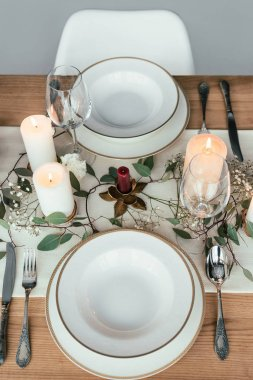 close up view of stylish table setting with candles, empty wineglasses and plates for rustic wedding
