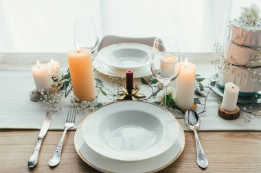 close up view of stylish table setting with candles, wineglasses and wedding cake for rustic wedding