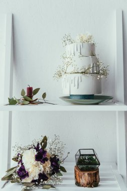 close up view of arranged wedding cake, bridal bouquet and wedding rings for rustic wedding