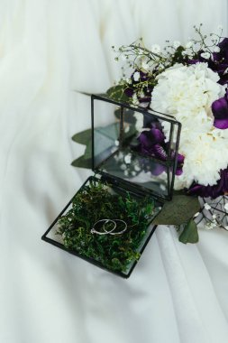close up view of wedding rings in rustic box and beautiful bridal bouquet on white linen