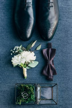 flat lay with arrangement of grooms shoes, bow tie, corsage and wedding rings for rustic wedding on blue background