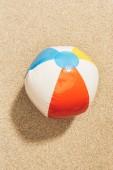 pohled shora na barevné nafukovací míč na písku