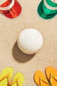 Photo flat lay with white volleyball ball, colorful caps and flip flops arranged on sand