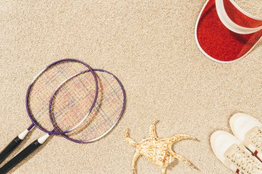 Top view of arrangement of badminton equipment, cap and shoes on sand stock vector