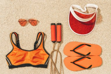 top view of arranged skipping rope, sportswear, sunglasses, cap and flip flops on sand