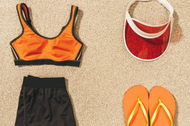 Top view of cap, flip flops and feminine sportswear arranged on sand stock vector