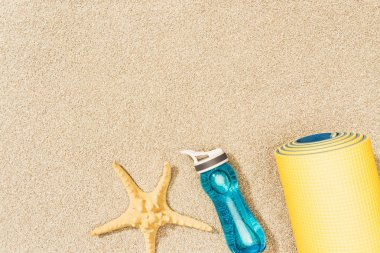 top view of yellow mat, water bottle and sea star on sand