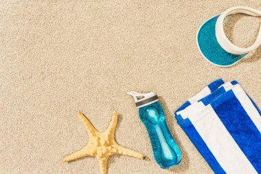 flat lay with sea star, water bottle, towel and cap arranged on sand