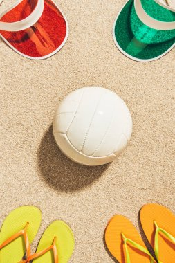 flat lay with white volleyball ball, colorful caps and flip flops arranged on sand
