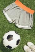 Fotografia lay flat con pallone da calcio, abbigliamento sportivo e scarpe da tennis su erba verde