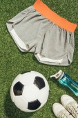 Fotografia lay flat con pallone da calcio, abbigliamento sportivo, bottiglia dacqua e scarpe da tennis su erba verde