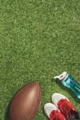 Fotografia lay flat con scarpe da ginnastica, pallone da rugby e bottiglia di acqua sul prato verde