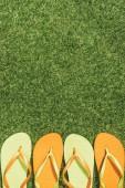 Blick von oben auf grüne und orangefarbene Flip Flops auf grünem Rasen