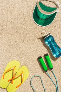 Top view of arranged cap, flip flops, water bottle and jump rope on sand stock vector