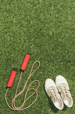 top view of arranged sneakers and skipping rope on green grass