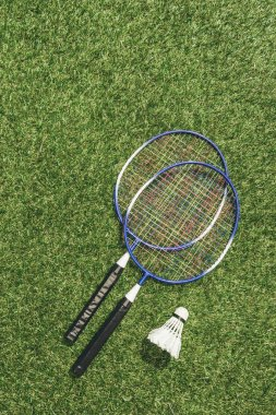 top view of badminton rackets and shuttlecock on green grass