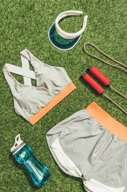 top view of arranged sportswear, water bottle, jump rope and cap on green grass