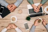 Top pohled na podnikatele, kteří pijí kávu s notebookem, smartphony a dokumenty na stole