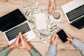 Pohled shora na obchodní partnery s notebooky a smartphonem podle kalkulačky na dolarových bankovkách na stole, oříznuté zobrazení