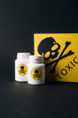 Photo Jars and card with toxic sign isolated on black