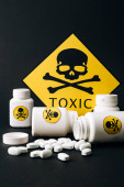 Photo Toxic sign with jars and pills isolated on black
