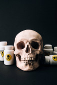Photo Skull and jars with poison sign isolated on black