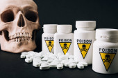 Photo Jars with poison sign by pills and skull isolated on black