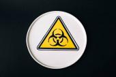 Horní pohled na štítek s nápisem biohazard izolovaný na černém