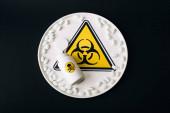 Horní pohled na nápis biohazard na talíři s pilulkami a lahví s jedovatým nápisem izolované na černé