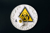 Top view of pills, syringe and jar on plate with biohazard sign isolated on black