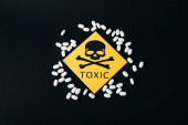 Photo Top view of pills and toxic sign isolated on black