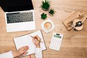 Top pohled na podnikatelku psaní v notebooku podle kalkulačky, notebook a káva na stole