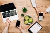 Top pohled na podnikatele pomocí chytrých telefonů a notebooku od jablek a schránky na stole