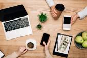 Top pohled na obchodní partnery pití kávy a používání chytrých telefonů notebookem a peníze na stole