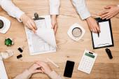 Az asztali kávéfőző mellett dokumentumokkal dolgozó üzleti partnerek áttekintése
