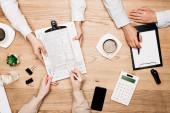 Horní pohled na podnikatele s papírováním, kalkulačkou a kávou na stole, ořezaný pohled