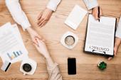Top pohled na obchodní partnery potřesení rukou v blízkosti smlouvy, káva a kreditní karty na stole