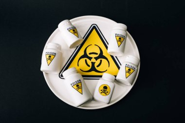 Top view of bottles with poison sign on plate with biohazard symbol isolated on black