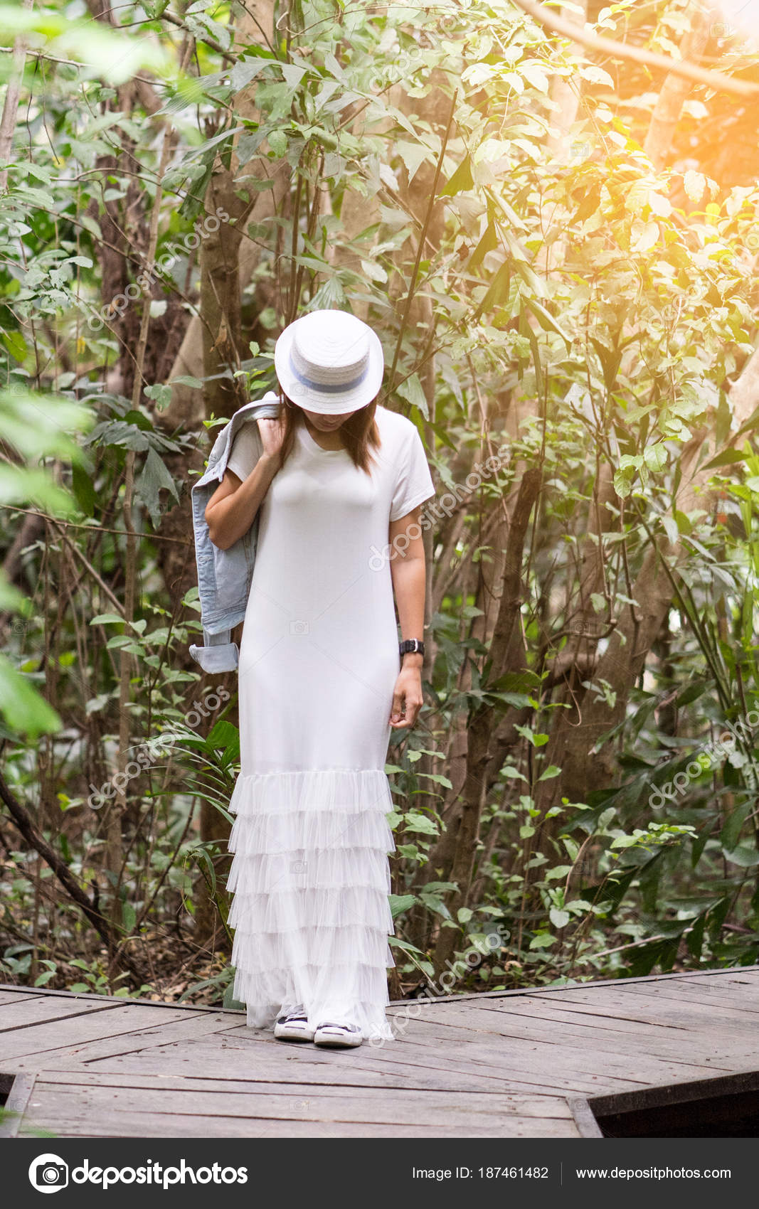377b754d1314 Ευτυχισμένη γυναίκα που φοράει λευκό μακρύ φόρεμα με σακάκι τζιν στο  δημόσιο πάρκο. Έννοια ευτυχισμένη ζωή με τη φύση– εικόνα αρχείου