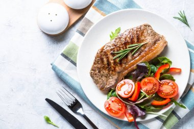 Grilled beef striploin steak with fresh salad. Healthy food lunch menu. Top view on light stone background. stock vector