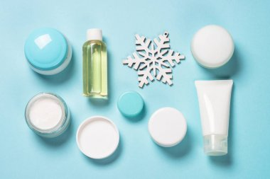 Winter cosmetics set on blue background flat lay. Winter cream for face, hands and body, skincare product. stock vector