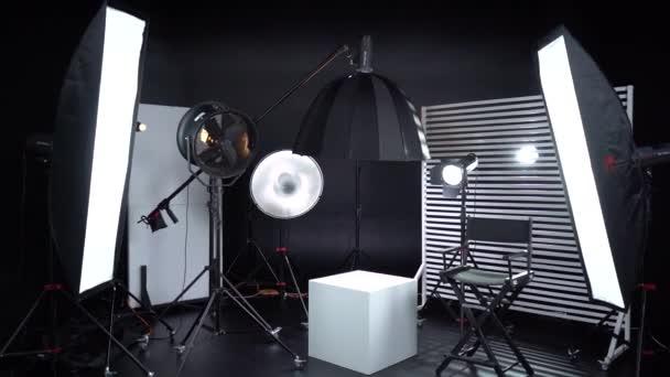 Black and White Cyclorama. Dark room. Modern photo studio with professional equipment. Empty photo studio with lighting equipment. Interior of modern photo studio with director production chair.