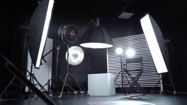 Schwarz-weißes Cyclorama. Dunkler Raum. Modernes Fotostudio mit professioneller Ausstattung. Leeres Fotostudio mit Beleuchtungsanlage. Interieur eines modernen Fotostudios mit Regiestuhl.