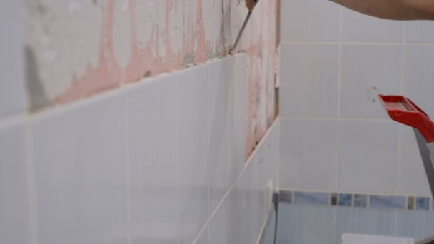 Il lavoratore rimuove le vecchie piastrelle di ceramica da muro