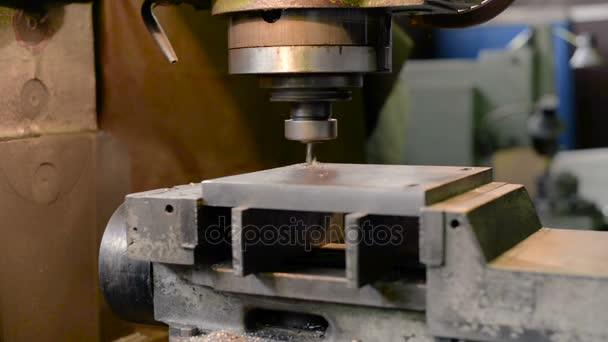 Vertical knee-type milling machine processes the metal workpiece.