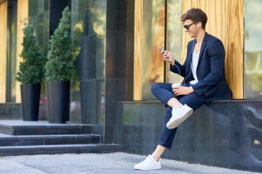 Side view portrait of stylish contemporary man relaxing outdoors enjoying music from  smartphone and smiling happily