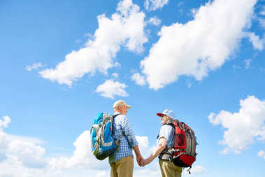 Back view portrait of active senior couple enjoying hiking trip together standing with big backpacks holding hands against background of clear blue sky