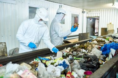 Portrait of two workers  wearing biohazard suits working at waste processing plant sorting trash on conveyor belt, copy space
