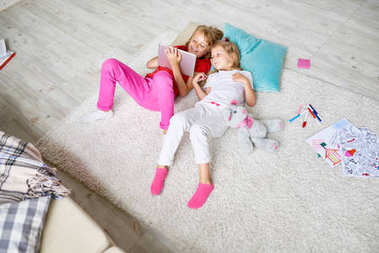 Above view portrait of two little girls using digital tablet  for watching cartoons while lying on floor in children room surrounded by toys and coloring pencils.