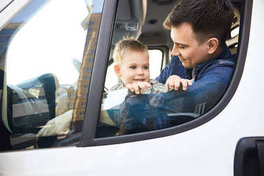 Portrait of cute little kid looking out of car window and smiling happily sitting on fathers lap